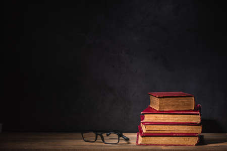 stack of old books and glasses on wooden table on black cement wall