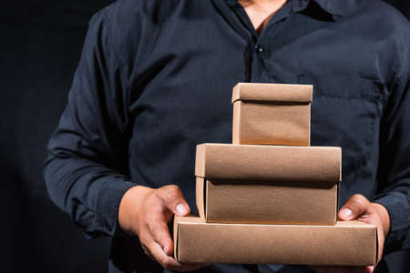 a man holding stack of different size craft boxes on black background