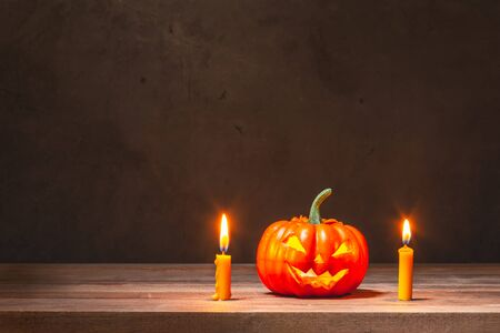halloween pumpkin and yellow candles on wooden table 스톡 콘텐츠
