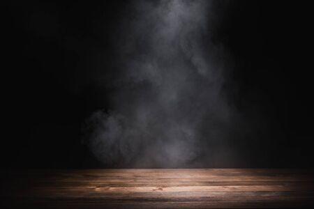 leerer Holztisch mit Rauch schweben auf dunklem Hintergrund Standard-Bild