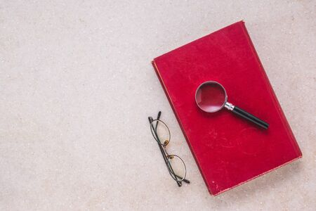 old book, magnifying glass and eye glasses on white marble table, top view Reklamní fotografie