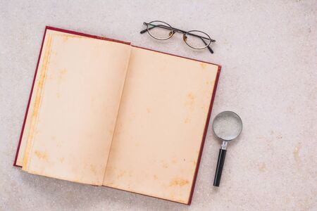 opened old book, magnifying glass and eye glasses on white marble table, top view