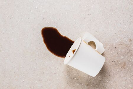 split coffee from a paper cup on terrazzo stone table, top view with copy space for text
