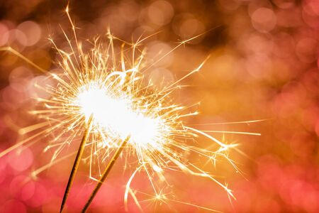 close-up of burning sparklers on beautiful bokeh background, christmas and new year festive concept
