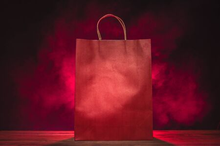red paper shopping bags on red smoke, abstract dark background Reklamní fotografie