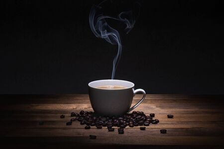 a cup of coffee and beans on wooden table, hot drink with steam Reklamní fotografie