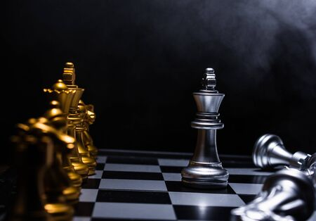 silver king chess piece face up to gold chess team on black background with smoke, challenger one leader staying on court Reklamní fotografie