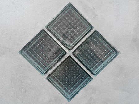 Rotated glass blocks with glass pixels on a concrete wall.