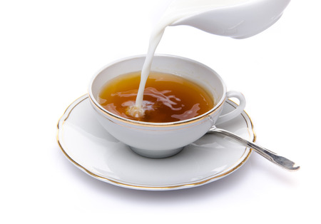 Milk poured into a cup of tea, isolated on white