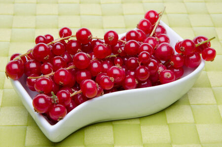 place mat: Redcurrants in a small dish on a green place mat