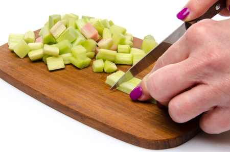 Woman s hand chopping rhubarb, isolated on white photo
