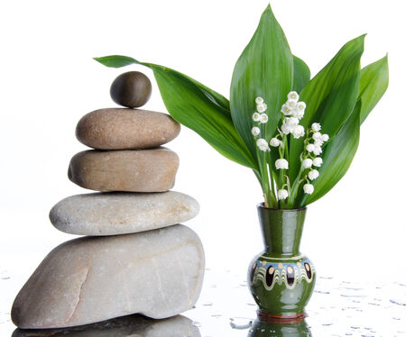 muguet: Composition of stacked pebbles with a vase of lilies, on a white wet background Stock Photo