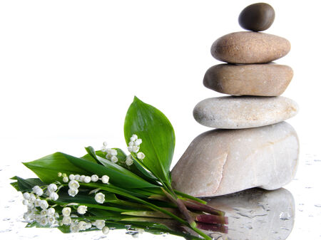muguet: Composition of stacked pebbles with a bouquet of lilies, on a white wet background