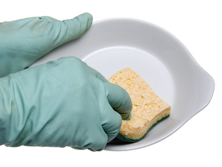 Hand with dish gloves cleaning a plate, isolated on white photo