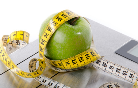 scales thin: Tape measure around a green apple on a bathroom scales, isolated on white Stock Photo