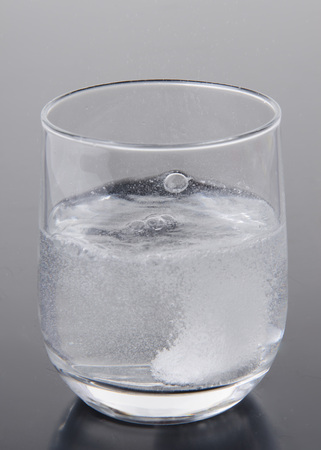 Effervescent tablet in a glass of water on a grey  photo