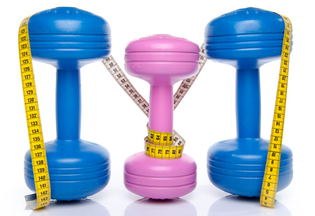 Pink and blue dumbells with a tape measure, isolated on white photo