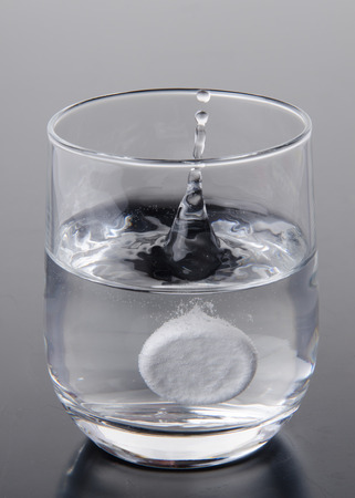 Effervescent tablet falling into a glass of water on a grey  photo