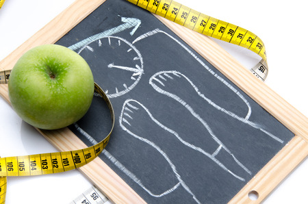 Concept of weight loss with an apple and a tape measure, isolated on white photo