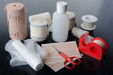 wound care: Different rolls of medical bandages and care equipment on a black background Stock Photo