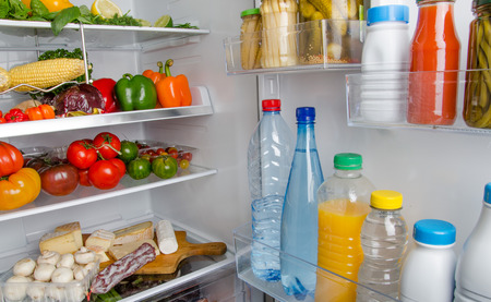 Part of a refrigerator full of different food products photo