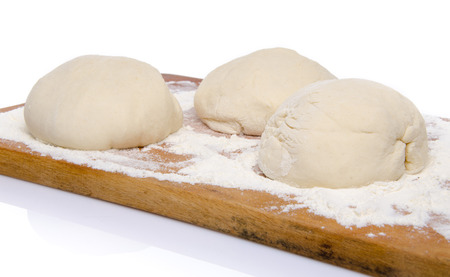 Three balls of pizza dough on a wooden board, isolated on white photo