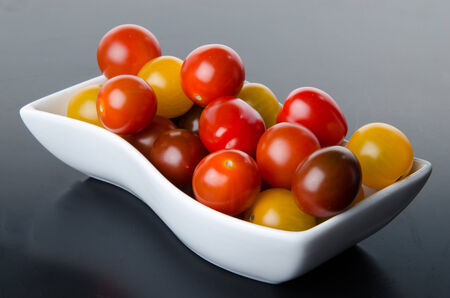 cherry varieties: Cup of different varieties of cherry tomatoes on a black background