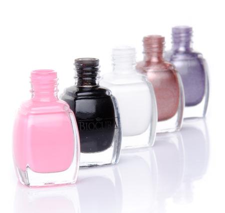 Line of nail polish bottles, isolated on white photo