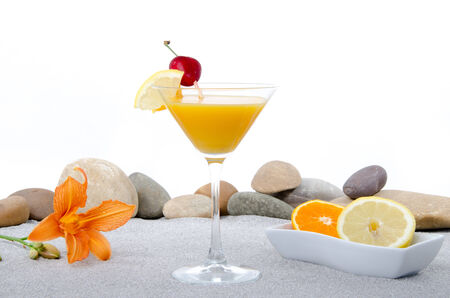 Composition with a orange cocktail, sand and pebble stones, isolated on white photo