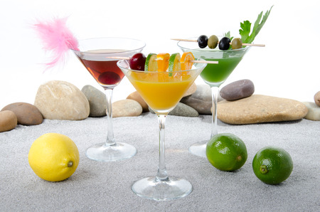 Composition with a orange, cherry and cucumber cocktails in a environment of sand and pebble stones photo
