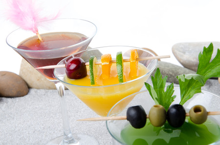 Composition with a orange, cherry and green vegetables cocktails on a beach environment photo