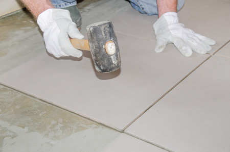 Laying floor tiles, tiler using a rubber mallet photo