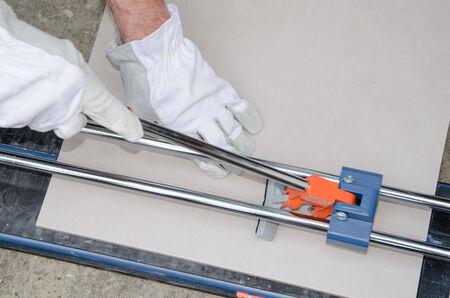 Laying floor tiles, tiler using a tile cutter Stock Photo
