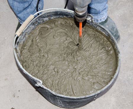 tile adhesive: Laying tiles, tiler mixing tile adhesive with power drill in a bucket Stock Photo