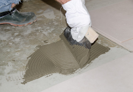 tile adhesive: Laying tiles, tiler spreading tile adhesive on the floor