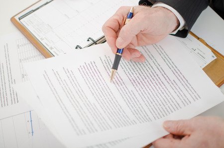 office documents: Businessman checking a document at his desk Stock Photo