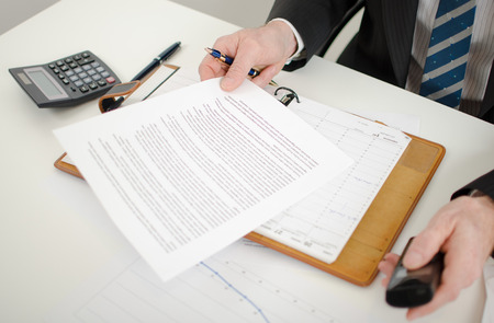 Businessman reading a document at his desk photo