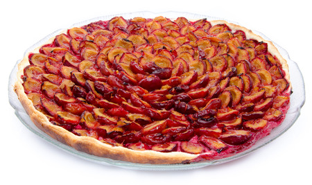 Tasty plum tart after baking, isolated on white photo