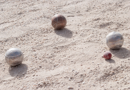 bocce: Metallic petanque balls and a small red jack on fine gravel