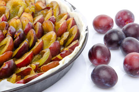 Plum tart before baking, isolated on white photo
