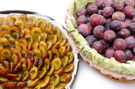 Plum tart before baking and a basket with fresh plums, isolated on white photo