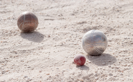 bocce ball: Metallic petanque balls and a small red jack on fine gravel
