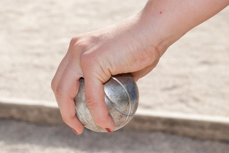 bocce ball: Human s hand holding a petanque ball before throwing it