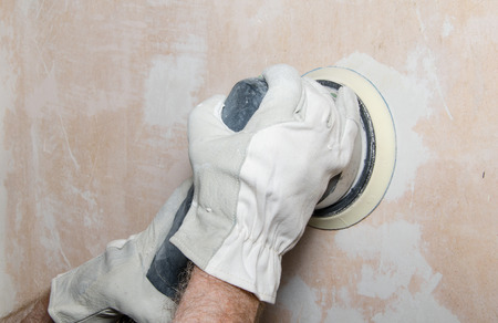Room repair,sanding of a wall with a power sander