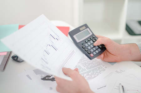 Businessman s hands with calculator at the office photo