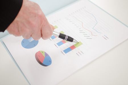 Hand showing a business graph with a pen photo
