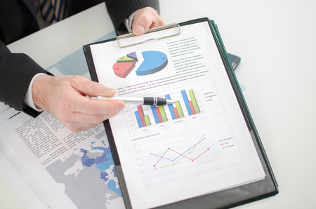 Businessman showing graphs at the office photo