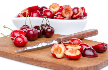 pitted: Composition with whole and pitted cherries, isolated on white