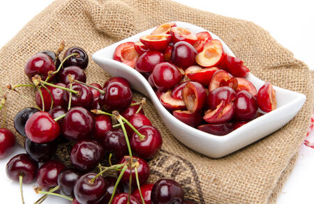 pitted: Cup of tasty pitted cherries and whole cherries on a burlap Stock Photo