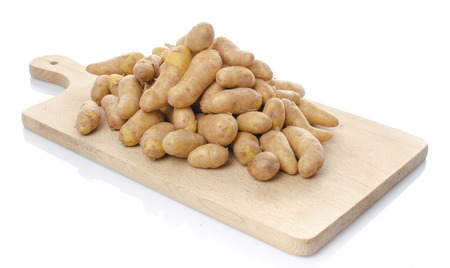 New rattes potatoes on a wooden board, isolated on white photo